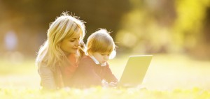 Mother and son using laptop outdoors.